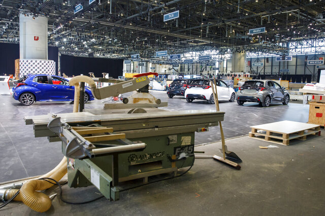 Cars are pictured as workers stop the preparation of the 90th Geneva International Motor Show, GIMS, at Palexpo, in Geneva, Switzerland, Friday, Feb. 28, 2020. The 90th edition of the International Motor Show, scheduled to begin on March 5th, is cancelled due to the advancement of the (Covid-19) coronavirus in Switzerland. The Swiss confederation announced today that all events involving more than 1,000 people would be banned until 15 March. (Salvatore di Nolfi/Keystone via AP)