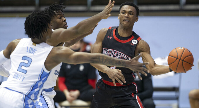 North Carolina's Day'Ron Sharpe (11) and Caleb Love (2) defend against Northeastern's Tyson Walker (2) during the second half of an NCAA college basketball game Wednesday, Feb. 17, 2021, in Chapel Hill, N.C. (Robert Willett/The News & Observer via AP)