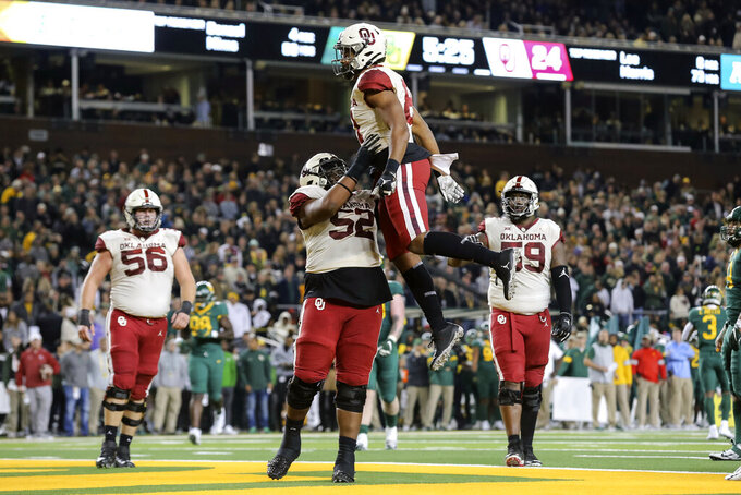 Oklahoma fullback Brayden Willis, center top, is lifted in the air by Oklahoma offensive lineman Tyrese Robinson, bottom center, after scoring a touchdown against Baylor during the second half of an NCAA college football game in Waco, Texas, Saturday, Nov. 16, 2019. Oklahoma won 34-31. (AP Photo/Ray Carlin)