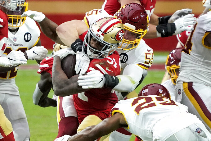 San Francisco 49ers running back Raheem Mostert (31) is hit by Washington Football Team linebacker Cole Holcomb (55) during the first half of an NFL football game, Sunday, Dec. 13, 2020, in Glendale, Ariz. (AP Photo/Rick Scuteri)