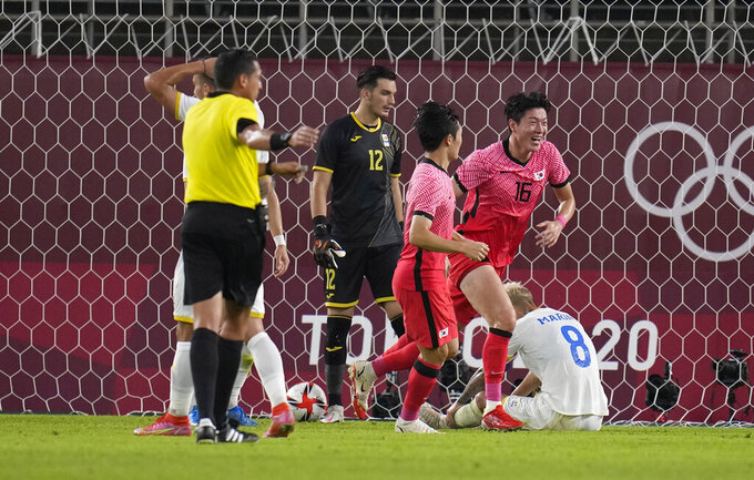 South Korea's Hwang Uijo (16) celebrates after a Romania own goal during a men's soccer match at the 2020 Summer Olympics, Sunday, July 25, 2021, in Kashima, Japan. (AP Photo/Fernando Vergara)