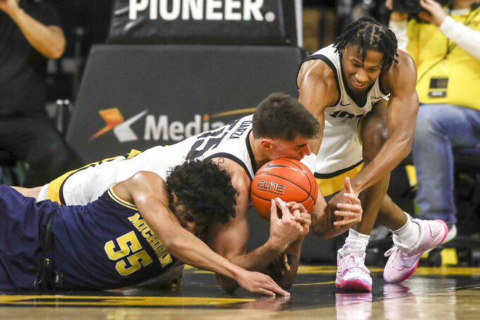 Iowa center Luka Garza (55) and guard Bakari Evelyn (4) and Michigan guard Eli Brooks (55) go after the ball during the firt half of an NCAA college basketball game Friday, Jan. 17, 2020, in Iowa City, Iowa. (Rebecca F. Miller/The Gazette via AP)