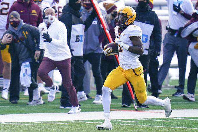 Minnesota head coach P.J. Fleck runs alongside running back Cam Wiley (1) during the first half of an NCAA college football game against Nebraska in Lincoln, Neb., Saturday, Dec. 12, 2020. (AP Photo/Nati Harnik)