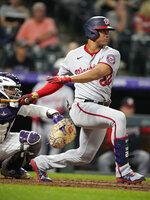 Washington Nationals' Juan Soto hits into a force play but drives in a run against Colorado Rockies starting pitcher German Marquez in the fifth inning of a baseball game Monday, Sept. 27, 2021, in Denver. (AP Photo/David Zalubowski)
