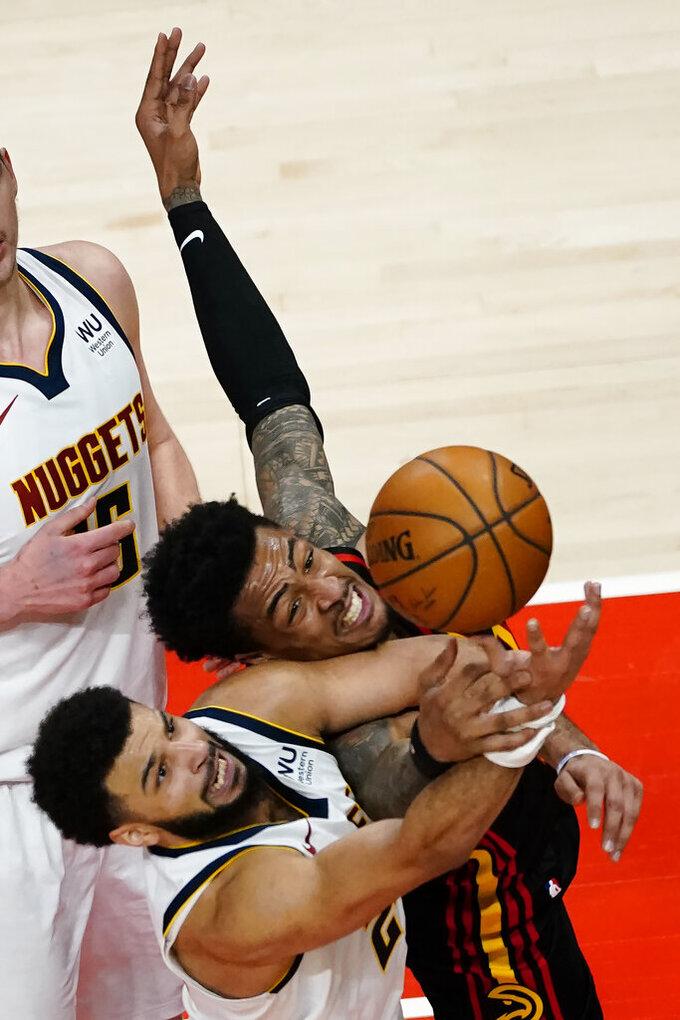 Denver Nuggets guard Jamal Murray, bottom, and Atlanta Hawks forward John Collins vie for a rebound during the second half of an NBA basketball game Sunday, Feb. 21, 2021, in Atlanta. (AP Photo/John Bazemore)