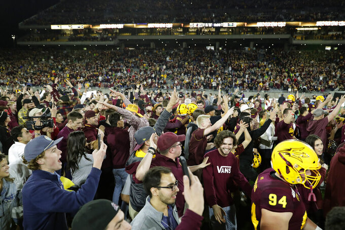 Arizona State fans rush the field after the team's NCAA college football game against Oregon, Saturday, Nov. 23, 2019, in Tempe, Ariz. Arizona State won 31-28. (AP Photo/Matt York)