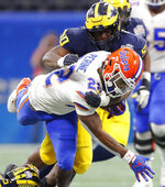 Michigan defensive lineman Michael Dwumfour (50) tackles Florida running back Lamical Perine (22) during the first half of the Peach Bowl NCAA college football game, Saturday, Dec. 29, 2018, in Atlanta. (AP Photo/John Bazemore)