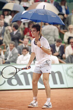 FILE - In this June 3, 1988, file photo, United States' Andre Agassi holds an umbrella and jokes with spectators during a short interruption due to rain while he was playing Mats Wilander of Sweden in a semifinal match of the French Open Tennis Tournament at Roland Garros Stadium in Paris. (AP Photo/Lionel Cironneau, File)