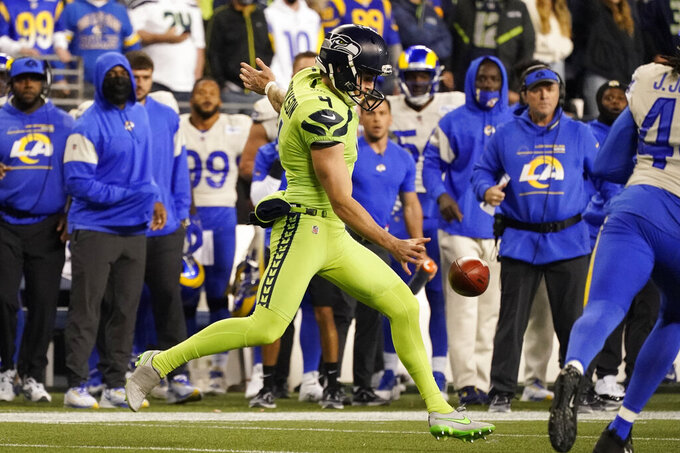 Seattle Seahawks punter Michael Dickson (4) kicks the ball a second time on the same play after his first kick was blocked by Los Angeles Rams' Jamir Jones during the second half of an NFL football game, Thursday, Oct. 7, 2021, in Seattle. The Seahawks were penalized for the second kick. (AP Photo/Elaine Thompson)