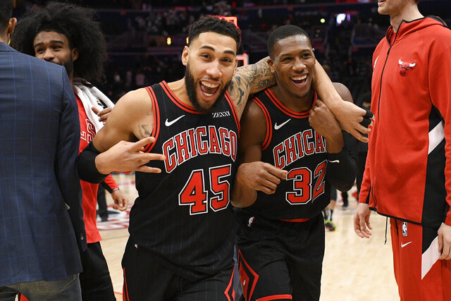 Chicago Bulls guards Kris Dunn (32) and Denzel Valentine (45) react after the team's NBA basketball game against the Washington Wizards, Wednesday, Dec. 18, 2019, in Washington. The Bulls won 110-109 in overtime. (AP Photo/Nick Wass)