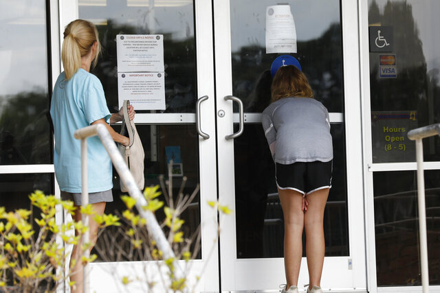Residents seeking driver's license renewals peer through the glass doors of a closed Drivers Service Bureau adjacent to the main offices of the Mississippi Highway Safety Patrol in Jackson, Miss., Wednesday, June 3, 2020. Statewide all driver license locations have been closed for several months due to the COVID-19 pandemic. (AP Photo/Rogelio V. Solis)