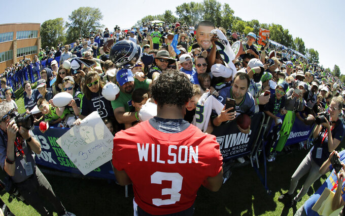 Seattle Seahawks quarterback Russell Wilson (3) signs autographs for fans following NFL football training camp, Thursday, July 25, 2019, in Renton, Wash. (AP Photo/Ted S. Warren)