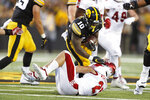 Iowa running back Mekhi Sargent (10) runs over Miami of Ohio defensive back Sterling Weatherford during the first half of an NCAA college football game, Saturday, Aug. 31, 2019, in Iowa City, Iowa. (AP Photo/Charlie Neibergall)