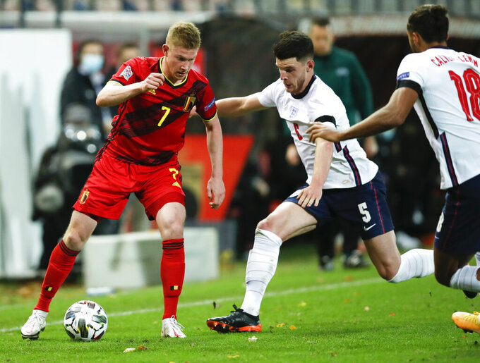 Belgium's Kevin De Bruyne, left, looks to pass the ball past England's Declan Rice and Dominic Calvert-Lewin, right, during the UEFA Nations League soccer match between Belgium and England at the King Power stadium in Leuven, Belgium, Sunday, Nov. 15, 2020. (AP Photo/Francisco Seco)