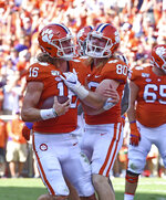 Clemson's Trevor Lawrence, left, and Luke Price celebrate Lawrence's touchdown during the first half of an NCAA college football game against Texas A&M, Saturday, Sept. 7, 2019, in Clemson, S.C. (AP Photo/Richard Shiro)