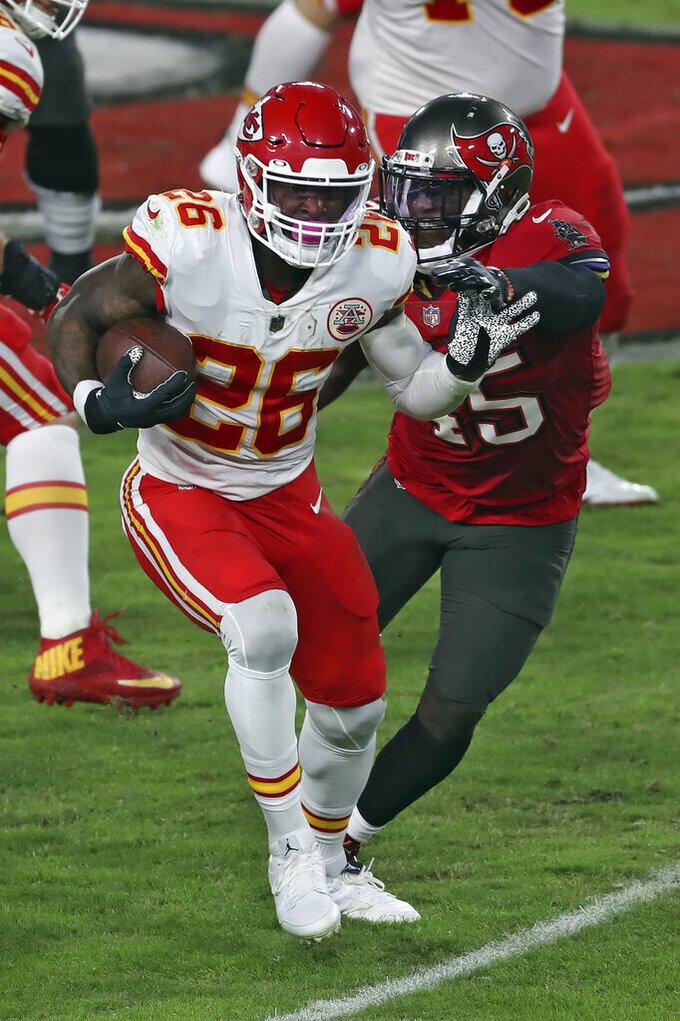 Kansas City Chiefs running back Le'Veon Bell (26) slips a tackle by Tampa Bay Buccaneers inside linebacker Devin White (45) during the first half of an NFL football game Sunday, Nov. 29, 2020, in Tampa, Fla. (AP Photo/Mark LoMoglio)