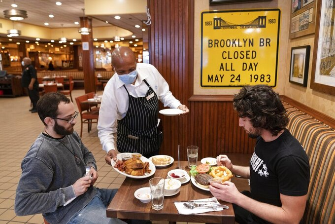 FILE - In this Sept. 30, 2020, file photo, Waiter Lenworth Thompson serves lunch to David Zennario, left, and Alex Ecklin at Junior's Restaurant in New York. New York Gov. Andrew Cuomo said Monday that city restaurants will be able to reopen for indoor dining at one-quarter capacity on Friday, Feb. 12, ahead of the Valentine's Day weekend, two days earlier than he'd previously announced. New York restaurants have been closed to indoor dining since Dec. 14, 2020, to stem a surge in coronavirus cases as the holidays approached. (AP Photo/Mark Lennihan, File)