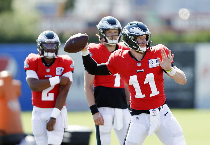 Philadelphia Eagles quarterback Carson Wentz (11) throws the football as backup quarterbacks Nate Sudfeld, center, and Jalen Hurts watch during an NFL football training camp practice in Philadelphia, Monday, Aug. 17, 2020. (Yong Kim/Pool Photo via AP)
