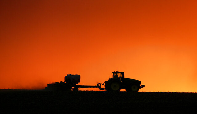 FILE - In this April 20, 2020, file photo, a farmer is silhouetted by the setting sun as a field is planted near Walford, Iowa. U.S. farmers across the nation leaned more heavily upon the federal government last year to finance their agricultural operations amid low commodity prices and trade disputes, and more of the money they borrowed from taxpayers is now delinquent. (Jim Slosiarek/The Gazette via AP, File)
