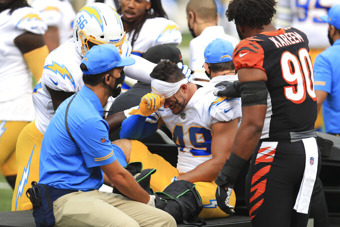 Los Angeles Chargers linebacker Drue Tranquill (49) is comforted by Kenneth Murray (56) and Cincinnati Bengals' Khalid Kareem (90) after being injured during the first half of an NFL football game, Sunday, Sept. 13, 2020, in Cincinnati. (AP Photo/Aaron Doster)