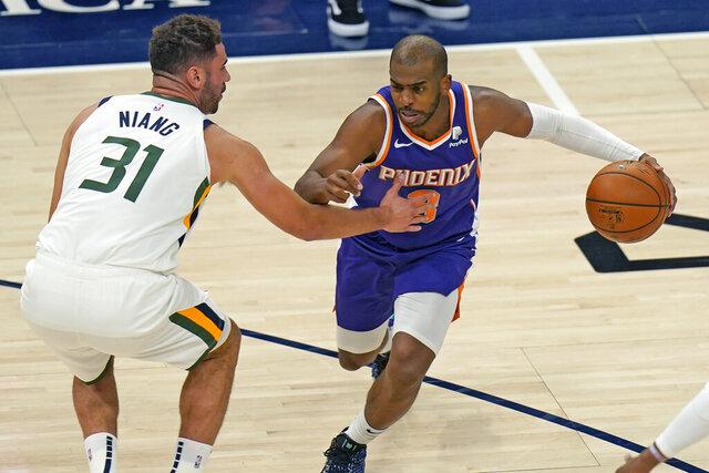 Phoenix Suns Chris Paul, right, drives as Utah Jazz forward Georges Niang, left,  defends during the first half of an NBA preseason basketball game Monday, Dec. 14, 2020, in Salt Lake City. (AP Photo/Rick Bowmer)