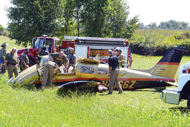 Investigators examine a single-engine Piper that crashed in a field off Airport Lake Road on Tuesday, Sept. 8, 2020, near Warren County Memorial Airport in McMinnville, Tenn. All three occupants were killed. (James Clark/Southern Standard via AP)