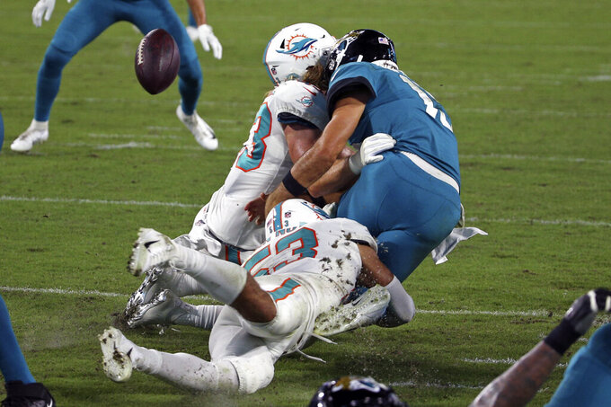 Jacksonville Jaguars quarterback Gardner Minshew, right, fumbles the ball as he is hit by Miami Dolphins outside linebacker Andrew Van Ginkel, left, and middle linebacker Kyle Van Noy during the second half of an NFL football game, Thursday, Sept. 24, 2020, in Jacksonville, Fla. (AP Photo/Stephen B. Morton)