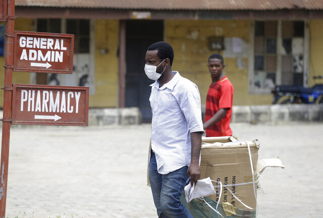 A man wearing face mask walks at the Yaba Mainland hospital where an Italian citizen who entered Nigeria on Tuesday from Milan on a business trip,  the first case of the COVID-19 virus is being treated in Lagos Nigeria Friday, Feb. 28, 2020. Nigeria's health authorities have reported the country's first case of a new coronavirus in Lagos, the first confirmed appearance of the disease in sub-Saharan Africa. (AP Photo/ Sunday Alamba)