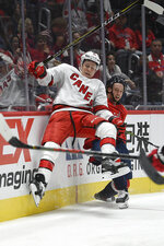 Carolina Hurricanes defenseman Jake Gardiner, left, and Washington Capitals left wing Brendan Leipsic, right, collide into the boards during the second period of an NHL hockey game, Saturday, Oct. 5, 2019, in Washington. (AP Photo/Nick Wass)