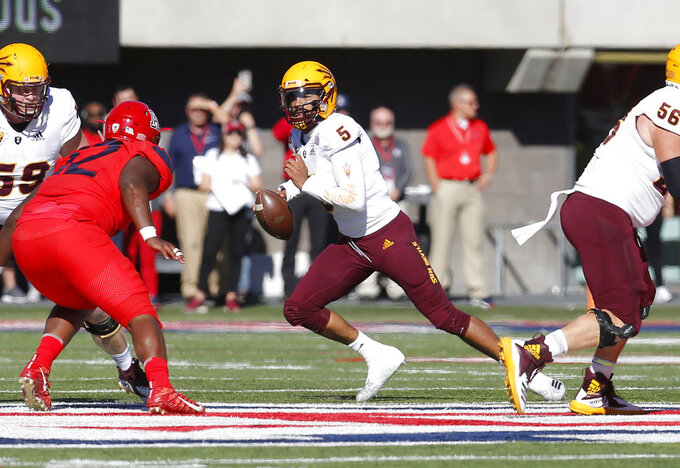 Arizona State quarterback Manny Wilkins (5) avoids a rush from the Arizona defense in the first half during an NCAA college football game, Saturday, Nov. 24, 2018, in Tucson, Ariz. (AP Photo/Rick Scuteri)