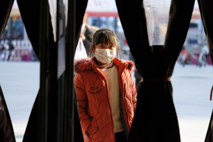A girl wearing a face mask stands in the entrance to a shop in Wuhan in central China's Hubei Province, Friday, Jan. 31, 2020. The U.S. advised against all travel to China as the number of cases of a worrying new virus spiked more than tenfold in a week, including the highest death toll in a 24-hour period reported Friday. (AP Photo/Arek Rataj)