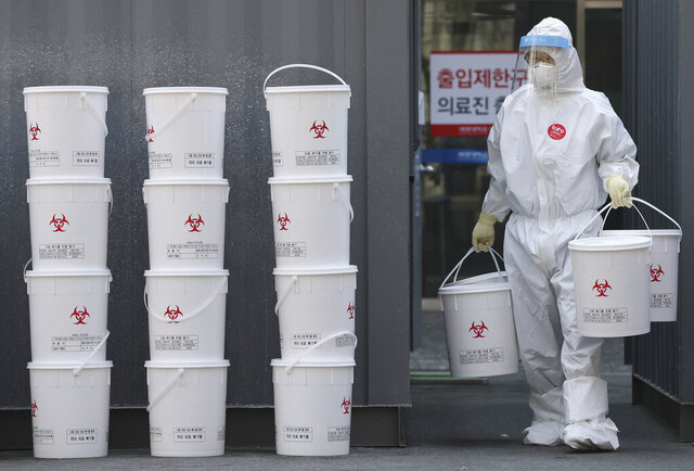 A staff member carries plastic buckets containing medical waste from new coronavirus patients at the Dongsan Hospital in Daegu, South Korea, Wednesday, March 25, 2020. For most people, the new coronavirus causes only mild or moderate symptoms, such as fever and cough. For some, especially older adults and people with existing health problems, it can cause more severe illness, including pneumonia. (Park Dong-joon/Yonhap via AP)
