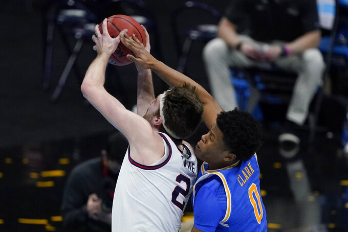 Gonzaga forward Drew Timme (2) is fouled by UCLA guard Jaylen Clark (0) while driving to the basket during the second half of a men's Final Four NCAA college basketball tournament semifinal game, Saturday, April 3, 2021, at Lucas Oil Stadium in Indianapolis. (AP Photo/Darron Cummings)
