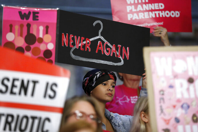 FILE - In this Tuesday, May 21, 2019 file photo, August Mulvihill, of Norwalk, Iowa, center, holds a sign depicting a wire clothes hanger during a rally at the Statehouse in Des Moines, Iowa, to protest recent abortion bans. On Wednesday, Nov. 6, 2019, a federal judge in New York struck down a rule letting health care clinicians object to providing abortions and other services on moral or religious grounds. (AP Photo/Charlie Neibergall)
