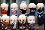 Face mask coverings to curb the spread of the coronavirus are displayed for sale on a section of 16th Street that's been renamed Black Lives Matter Plaza, Saturday, July 4, 2020, in Washington. (AP Photo/Maya Alleruzzo)