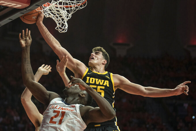 Iowa's Luca Garza (55) blocks the shot of Illinois' Kofi Cockburn (21) in the first half of an NCAA college basketball game Sunday, March 8, 2020, in Champaign, Ill. (AP Photo/Holly Hart)