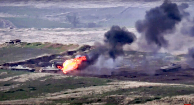 In this image taken from a footage released by Armenian Defense Ministry on Sunday, Sept. 27, 2020, Armenian forces destroy Azerbaijani military vehicle at the contact line of the self-proclaimed Republic of Nagorno-Karabakh, Azerbaijan. Fighting between Armenia and Azerbaijan has broken out around the separatist region of Nagorno-Karabakh and the Armenian Defense Ministry says two Azerbaijani helicopters have been shot down. Ministry spokeswoman Shushan Stepanyan also said Armenian forces hit three Azerbaijani tanks. (Armenian Defense Ministry via AP)