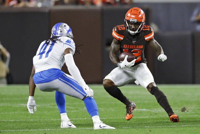 Cleveland Browns wide receiver Braxton Miller (12) avoids a tackle by Detroit Lions defensive back Johnathan Alston (41) during the first half of an NFL preseason football game Thursday, Aug. 29, 2019, in Cleveland. (AP Photo/Ron Schwane)