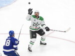 Dallas Stars defenseman Joel Hanley (39) grabs for the puck as Tampa Bay Lightning left wing Ondrej Palat (18) skates in during the third period of Game 5 of the NHL hockey Stanley Cup Final, Saturday, Sept. 26, 2020, in Edmonton, Alberta. (Jason Franson/The Canadian Press via AP)
