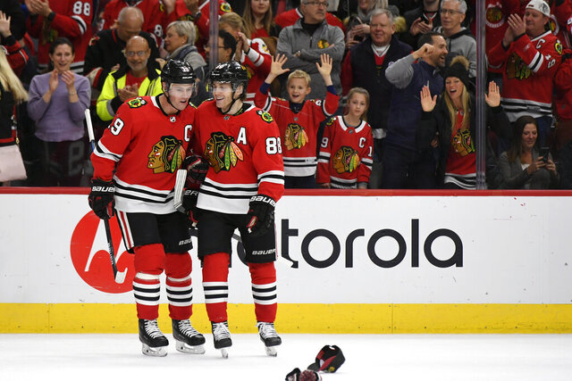 Chicago Blackhawks' Patrick Kane (88) celebrates with teammate Jonathan Toews (19) after scoring a hat trick during the third period of an NHL hockey game against the Minnesota Wild, Sunday, Dec. 15, 2019, in Chicago. (AP Photo/Paul Beaty)