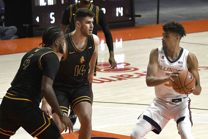 Illinois' Jacob Grandson (3) looks to pass the ball as North Carolina A&T's Quentin Jones (4) and Harry Morrice (14) defend during the first half of an NCAA college basketball game Wednesday, Nov. 25, 2020, in Champaign, Ill. (Photo/Holly Hart)