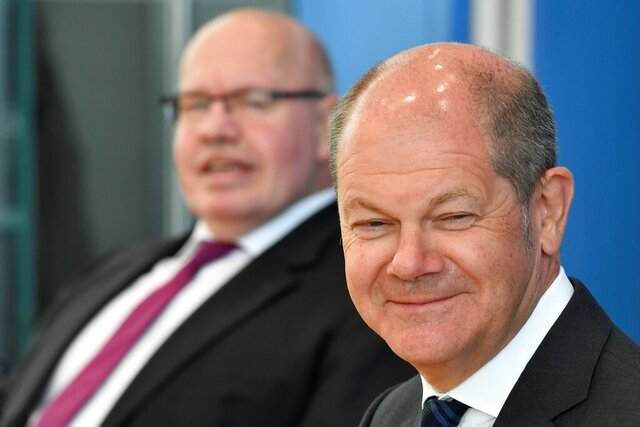 German Economy Minister Peter Altmaier, left, and German Finance Minister and Vice-Chancellor Olaf Scholz arrive to give a press conference on an aid package in response to the COVID-19 coronavirus pandemic, in Berlin, Monday April 6, 2020.  Restrictions on civil liberties and social restrictions have been imposed in many countries as the highly contagious COVID-19 coronavirus sweeps the globe. (John Macdougall/Pool via AP)