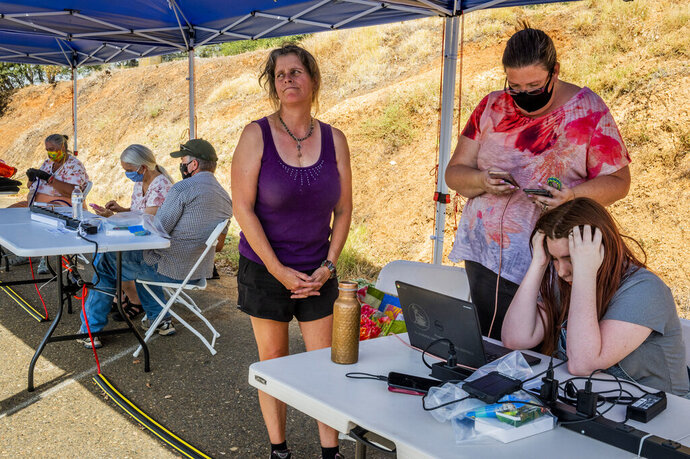 Helina Thorp, right, 14, expresses frustration while unsuccessfully trying to log in to her school distance-learning classes while her mother, Virginia Thorp, attempts to call school officials from a Pacific Gas & Electric community resource center at the El Dorado Fairgrounds during a Public Safety Power Shutoff in Placerville, Calif., on Tuesday, Sept. 8, 2020. People in nearly 172,000 homes and businesses in parts of California were sweltering Tuesday without electricity as Pacific Gas & Electric intentionally shut off power to prevent wildfires amid high winds. The business and household customers without power were in areas including the Sacramento Valley, Sierra Nevada foothills, and parts of Napa and Sonoma counties in wine country. (Daniel Kim/The Sacramento Bee via AP)