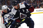 Colorado Avalanche defenseman Erik Johnson, front, fights for control of the puck in the corner with Winnipeg Jets center Mark Scheifele during the second period of an NHL hockey game Tuesday, Dec. 31, 2019, in Denver. (AP Photo/David Zalubowski)