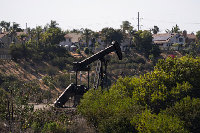 Homes are seen behind a pump jack operating at the Inglewood Oil Field in Los Angeles, Tuesday, May 18, 2021. California Gov. Gavin Newsom has set some of the nation's most ambitious goals for weaning his state off oil, including a ban on the sale of new gas-powered cars by 2035 and the end of oil production a decade later. (AP Photo/Jae C. Hong)