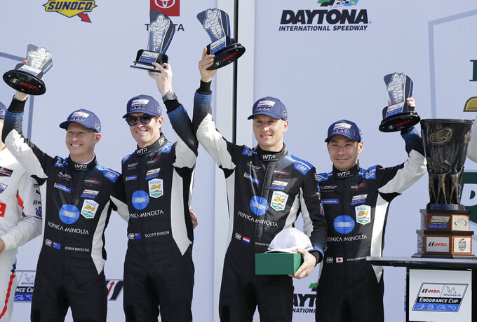 From left to right, Konica Minolta Cadillac DPi-V.R drivers Ryan Briscoe, Scott Dixon, Renger van der Zande, and Kamui Kobayashi hold up their trophies in Victory Lane after winning the Rolex 24-hour auto race at Daytona International Speedway, Sunday, Jan. 26, 2020, in Daytona Beach, Fla. (AP Photo/Terry Renna)