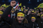 FILE - In this  Jan. 5, 2020 file photo, supporters of Hezbollah leader Sayyed Hassan Nasrallah chant slogans ahead of the leader's televised speech in a southern suburb of Beirut, Lebanon. The headbands read,