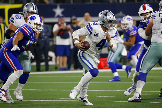 Dallas Cowboys quarterback Dak Prescott (4) is chased out of the pocket by the Buffalo Bills defense in the second half of an NFL football game in Arlington, Texas, Thursday, Nov. 28, 2019. (AP Photo/Michael Ainsworth)