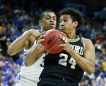 Wofford forward Keve Aluma (24) looks for a path to the basket against Kentucky's Keldon Johnson during the first half of a second-round game in the NCAA men's college basketball tournament in Jacksonville, Fla., Saturday, March 23, 2019. (AP Photo/Stephen B. Morton)