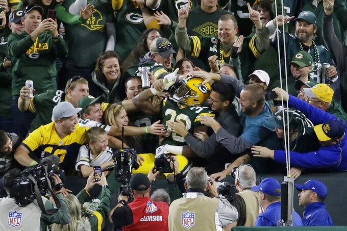 Green Bay Packers running back Aaron Jones celebrates and is congratulated by fans after his rushing touchdown during the first half of the team's NFL football game against the Philadelphia Eagles on Thursday, Sept. 26, 2019, in Green Bay, Wis. (AP Photo/Mike Roemer)